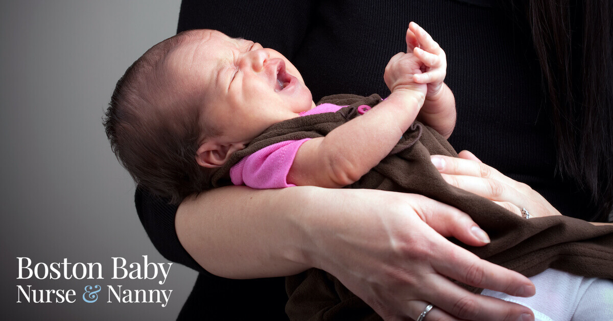 infant crying in mom's arms