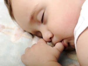 baby sleeping and sucking thumb