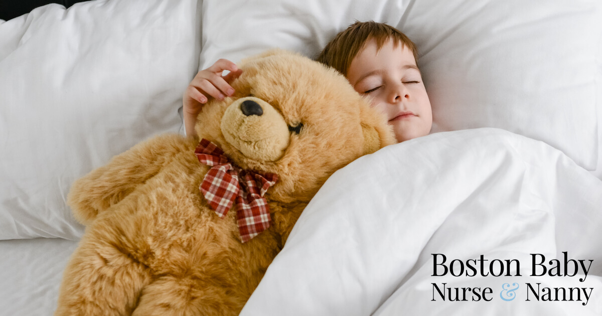 boy snuggling with his teddy in bed