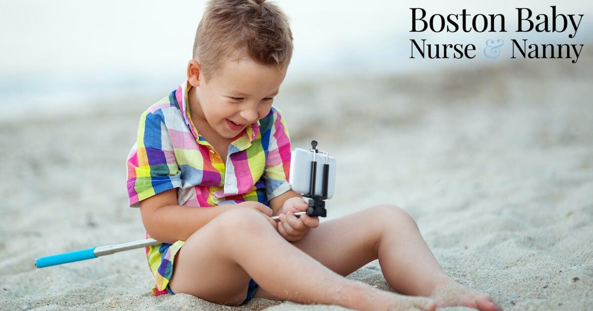 child using selfie stick on beach